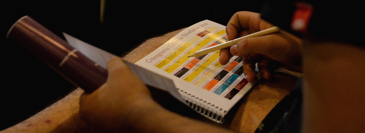 Un estudiante apunta algo en una agenda del Ciclo de Nivelación