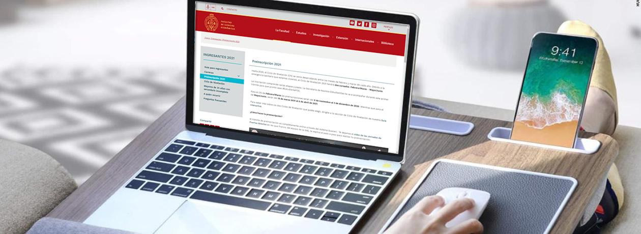 Una computadora portátil con la imagen de la página web donde se realizan las preinscripciones de la facultad, junto a un teléfono celular y un mouse con una mano de una mujer