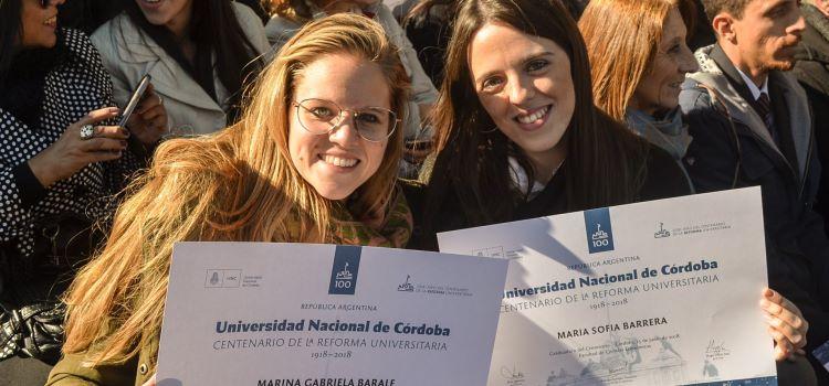 Dos egresadas de bachiller universitario muestran sus diplomas en un día soleado