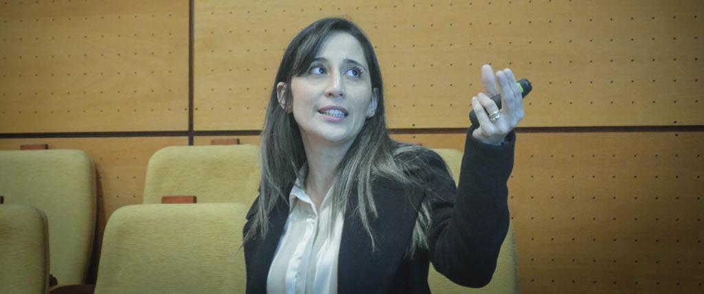 Imagen de la flamante doctora Alejandra Moreno López señalando con un puntero láser hacia la pared de proyección