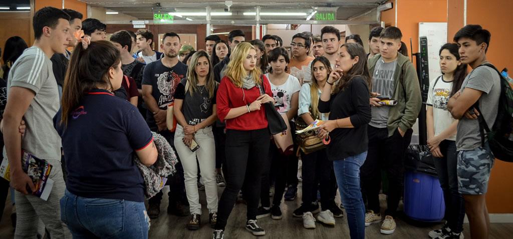 La licenciada Tatiana Rodríguez Castagno guía a los jóvenes dentro de la Biblioteca Manuel Belgrano de la Facultad