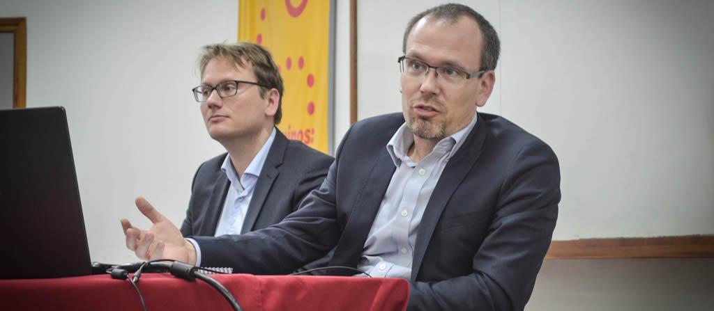 Imagen de Robert Grundke y Jens Arnolds exponiendo el Estudio Económico de la OCDE para Argentina en el aula bordó de la Secretaría de Extensión de la Facultad de Ciencias Económicas