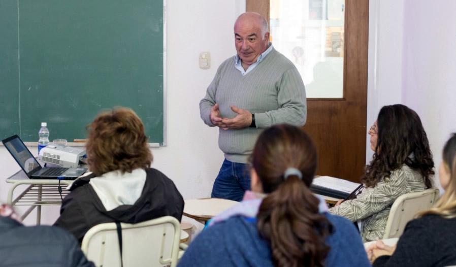 El profesor Nicolás Beltramino, de pulover color gris, exponiendo en una clase frente a cuatro mujeres