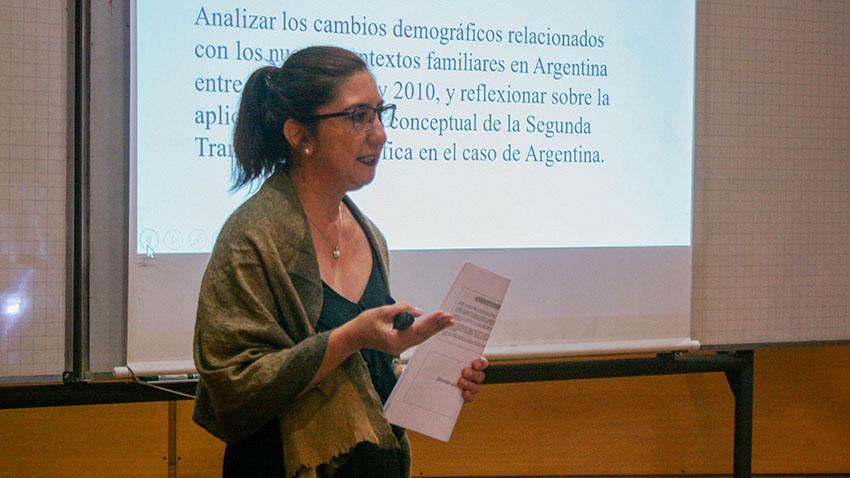 Eliana Soto expone su tesis con un papel en la mano y una pantalla gigante detrás