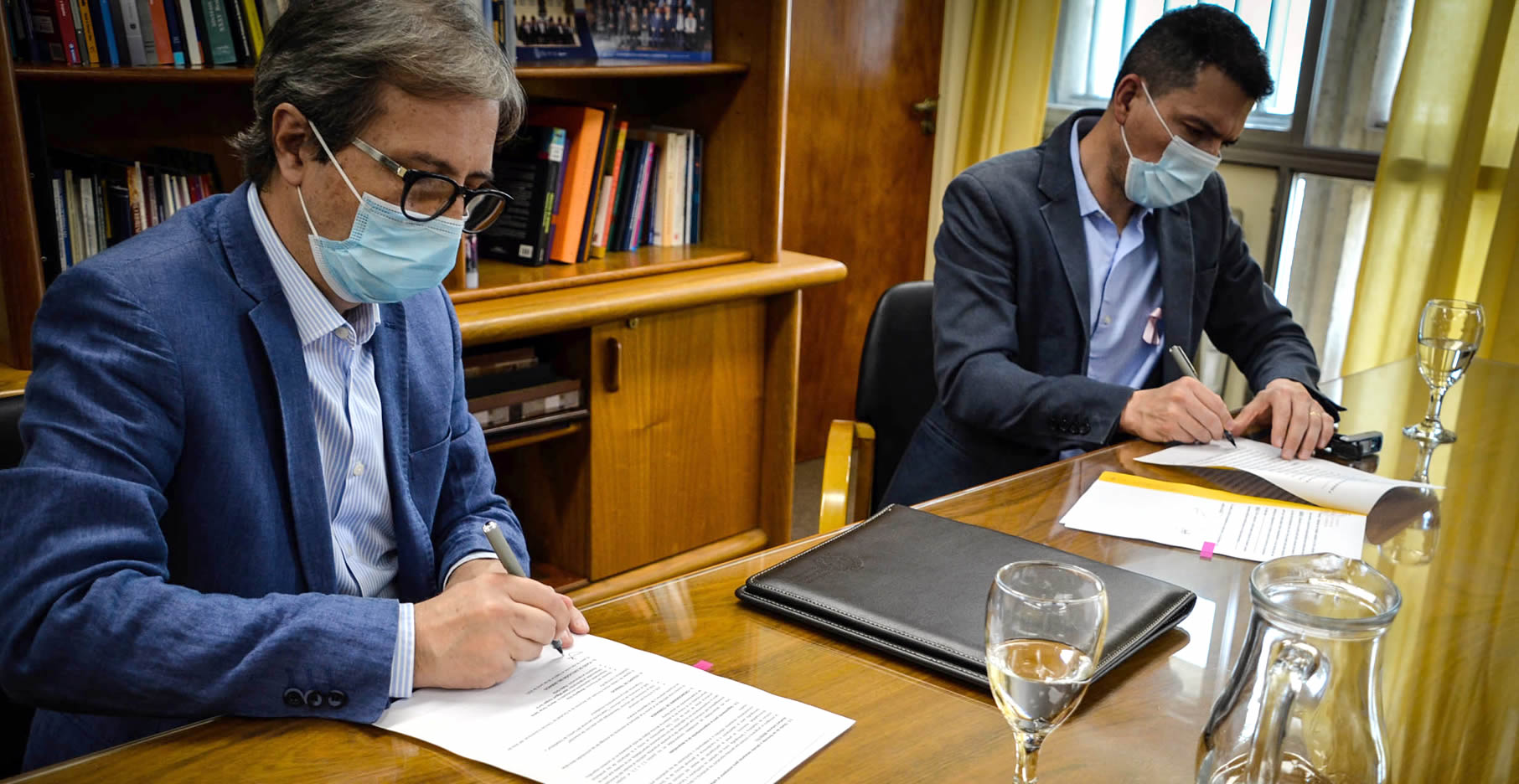 Jhon Boretto y Luis Picat, con barbijos, sentados firmando el convenio