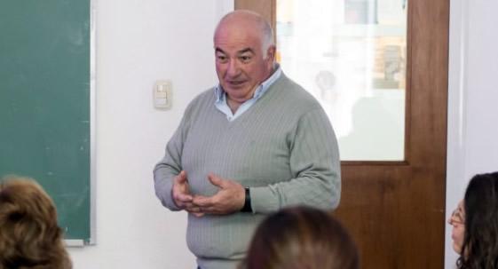 El profesor Beltramino explica en una clase. Se encuentra de pie con las manos entrelazadas y viste un pulover color gris