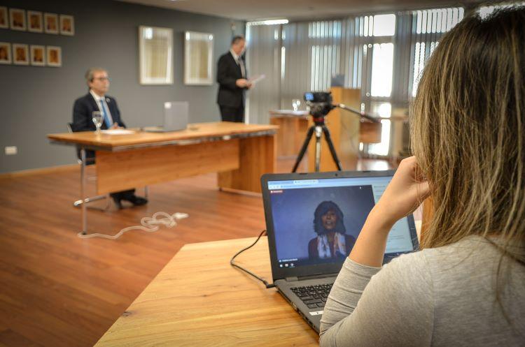 En una colación virtual, el Decano Jhon Boretto sentado frente a una computadora, el locutor ceremonial de pie leyendo un papel y más cerca una mujer viendo una computadora con la imagen de la Vicedecana Catalina Alberto