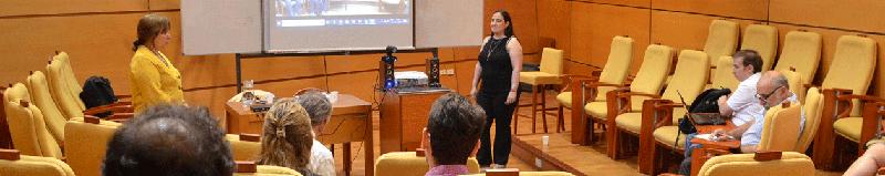 Una doctoranda de pie defendiendo su tesis en un auditorio de la Escuela de Graduados ante la mirada de una decena de personas presentes