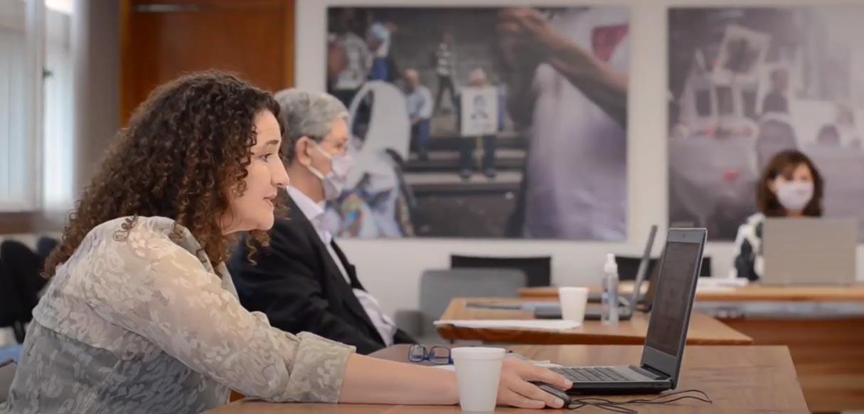 En una sala, de día, con paredes con dos grandes cuadros, la doctora Funes sentada hablando frente a una computadora portátil. Detrás está el doctor Zanazzi sentado, con barbijo, frente a una computadora portátil y a tres metros también sentada, con barbijo, está la vicedecana Catalina Alberto mirando su computadora portátil