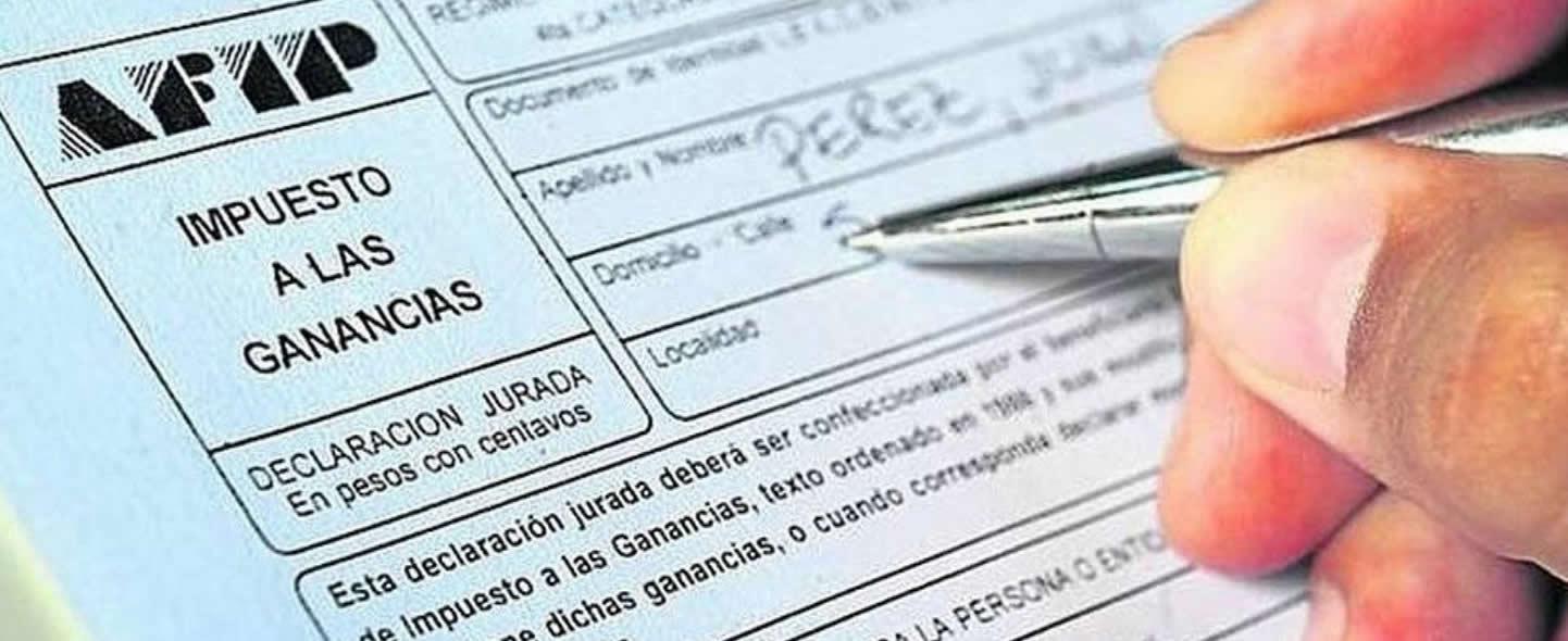 La mano de un varón con una lapicera llenando un formulario de AFIP