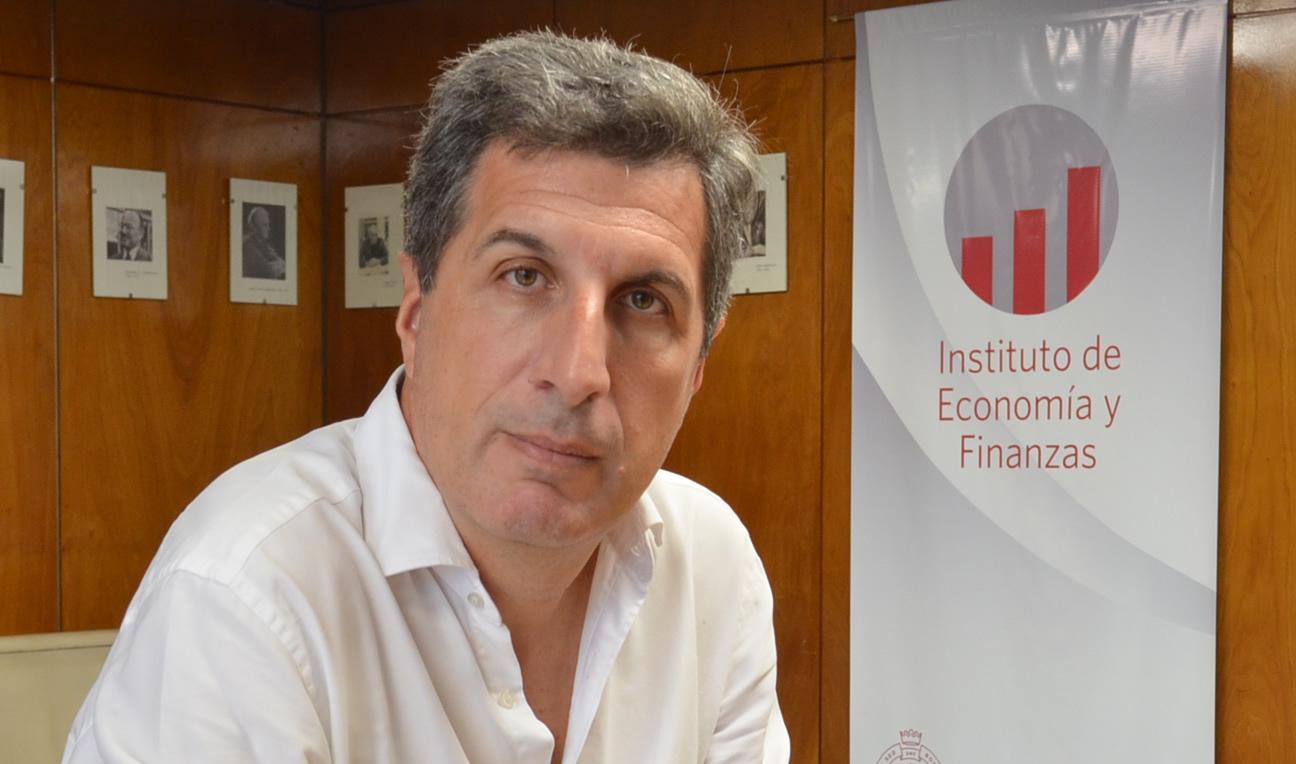 Alejandro Jacobo sentado y detrás el logo del Instituto de Economía y Finanzas