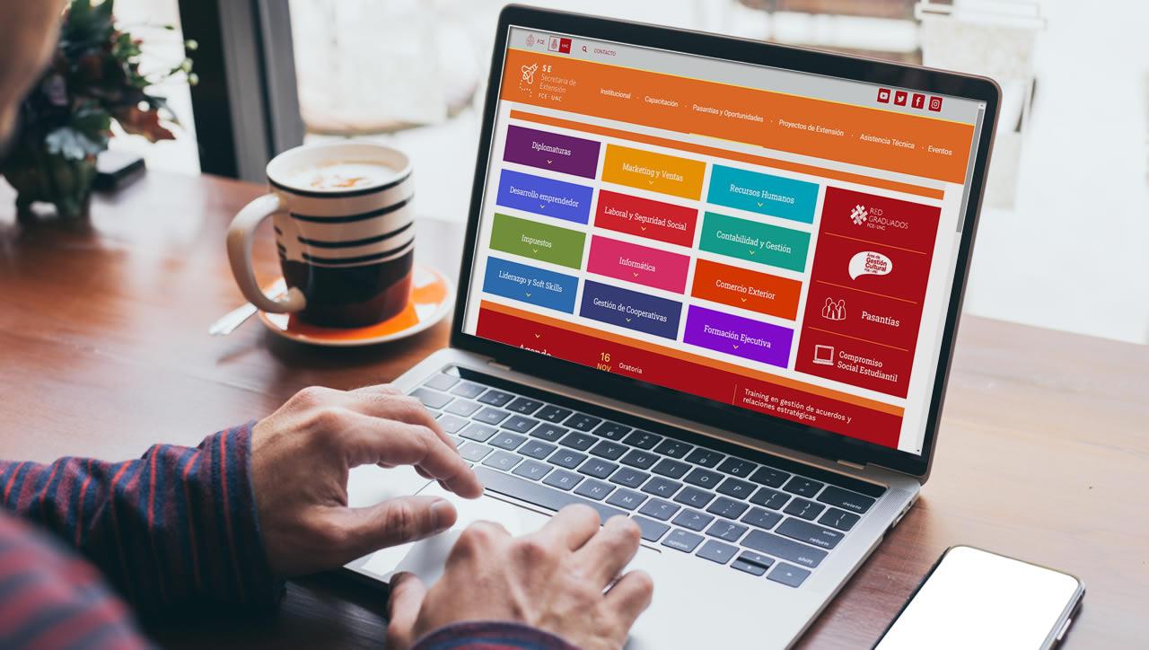 Una persona frente a una computadora portátil con la página web nueva de la Secretaría de Extensión y una taza de café al lado