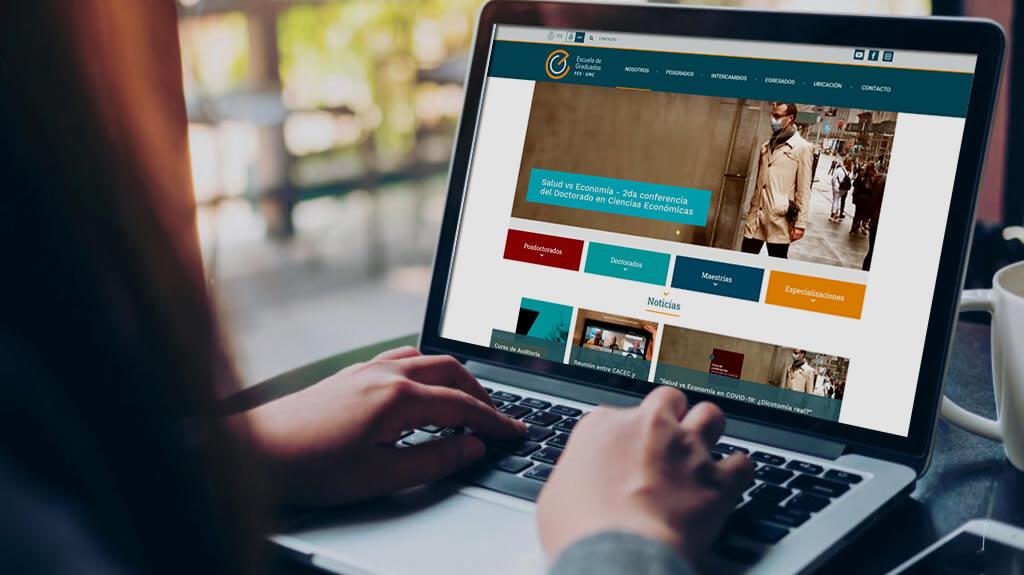 Una mujer con una computadora portátil navegando en la web de la Escuela de Graduados