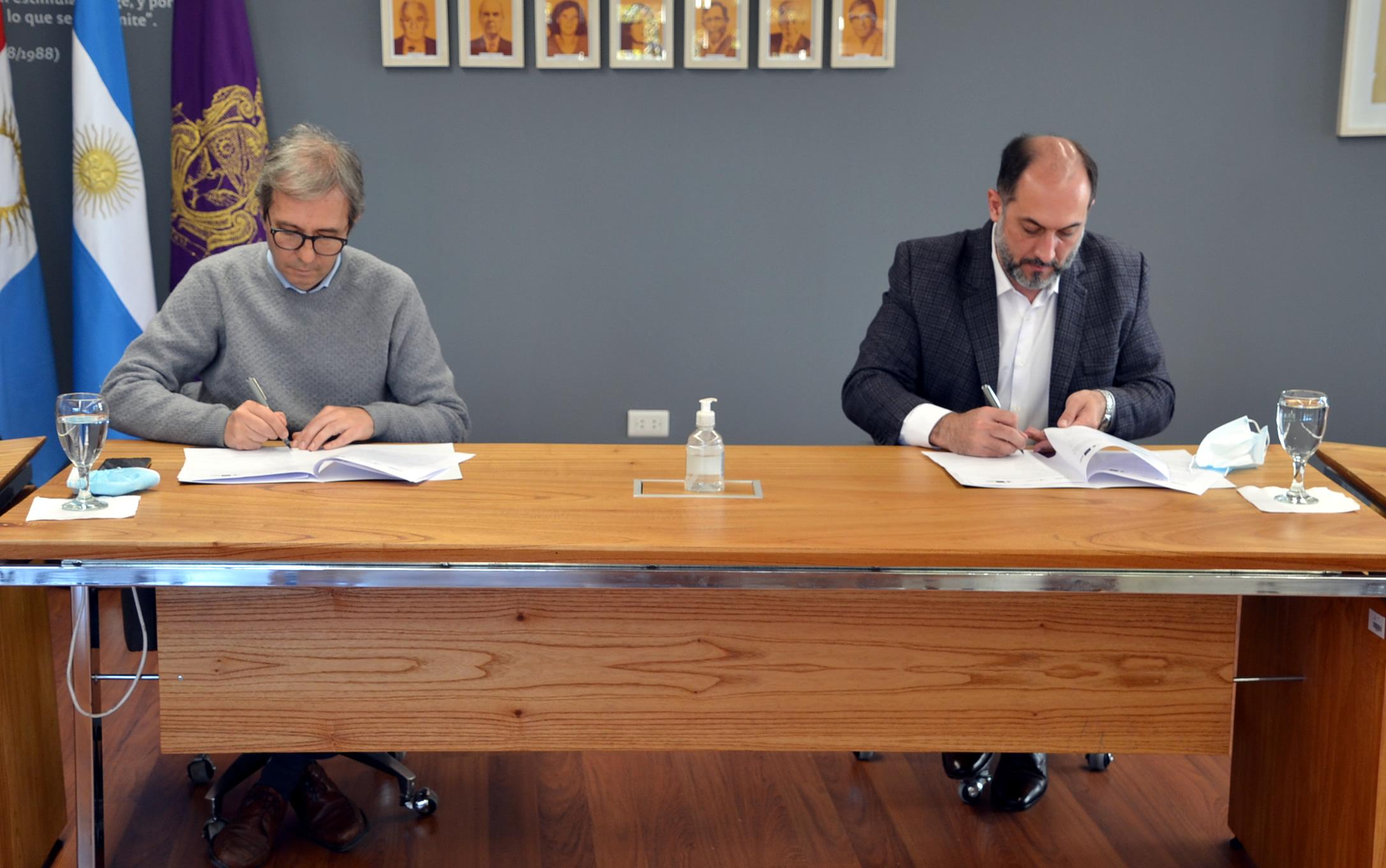 Jhon Boretto y Guillermo Acosta sentados firmando papeles sobre una mesa donde hay alcohol en gel, dos copas con agua, y sus respectivos barbijos, y detrás están las banderas de Argentina, la Provincia de Córdoba y la Universidad Nacional de Córdoba