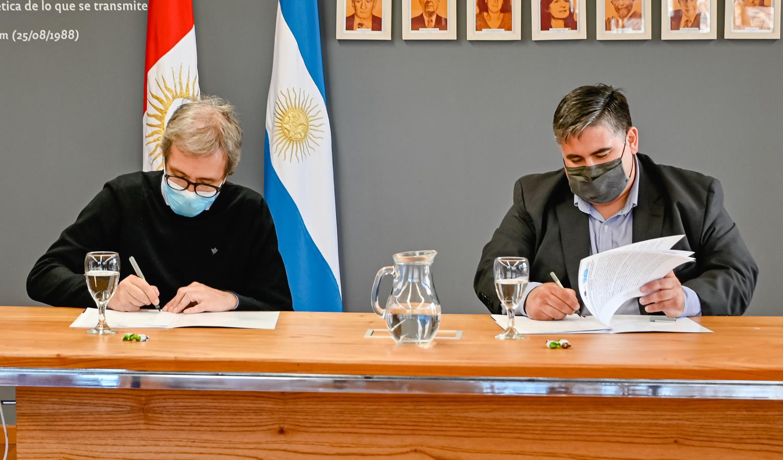 Jhon Boretto y Enzo Cravero, sentados y con barbijo, firmando copias del convenio específico