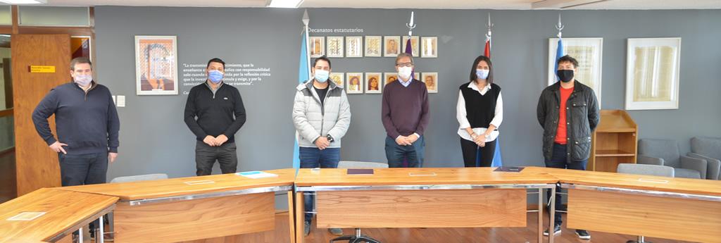 El señor Anconetani y el decano Boretto al medio rodeados de los demás participantes de la firma del acta acuerdo, todos de pie, en un día soleado en la sala Camilo Dagum