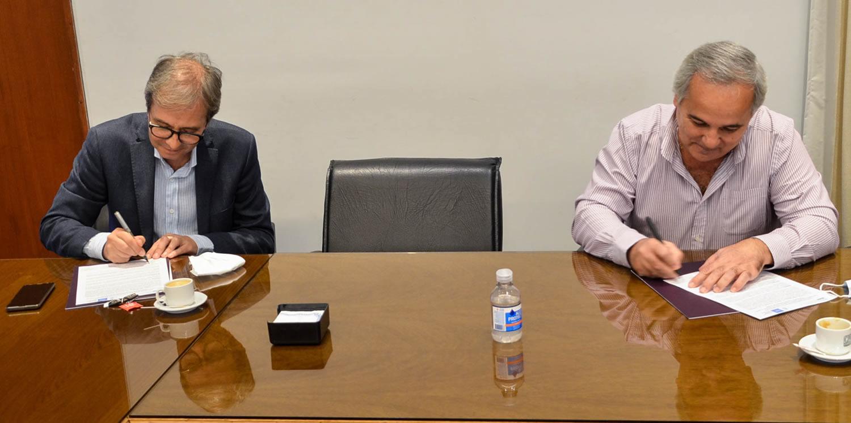 El Decano y el presidente del Consejo Profesional firman los papeles del convenio sobre una mesa con vidrio y separados por una silla vacía