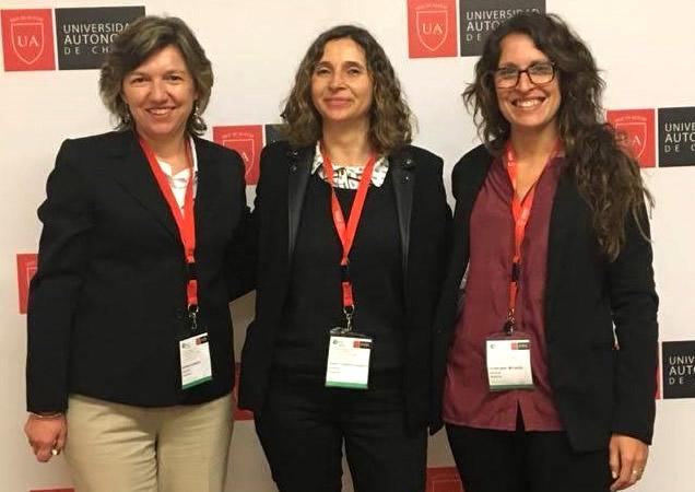 Mónica Buraschi, Florencia Peretti y Celina Amato sonrientes de pie con tiras porta identificación que cuelgan de su cuello en el marco de un congreso