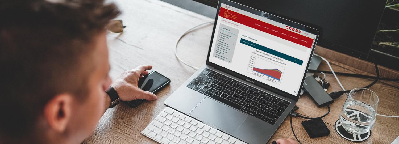 Un varón sentado maneja una computadora portátil que muestra el Portal de Transparencia con un cuadro con cifras y en la mesa hay un vaso con agua, un teléfono celular, un teclado inalámbrico, un mouse y es de día