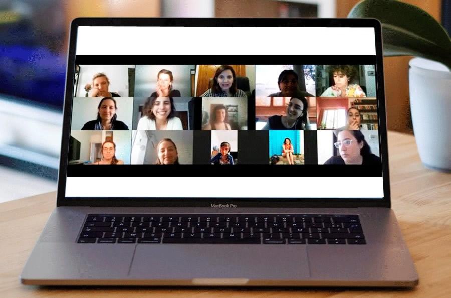 Una computadora portátil sobre una mesa de madera y en la pantalla hay una videoconferencia con varias personas conectadas
