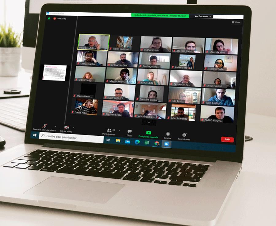Una computadora portátil en una mesa, en un día luminoso, conectada a una sesión se Google Meet donde se encuentran en línea una treintena de personas