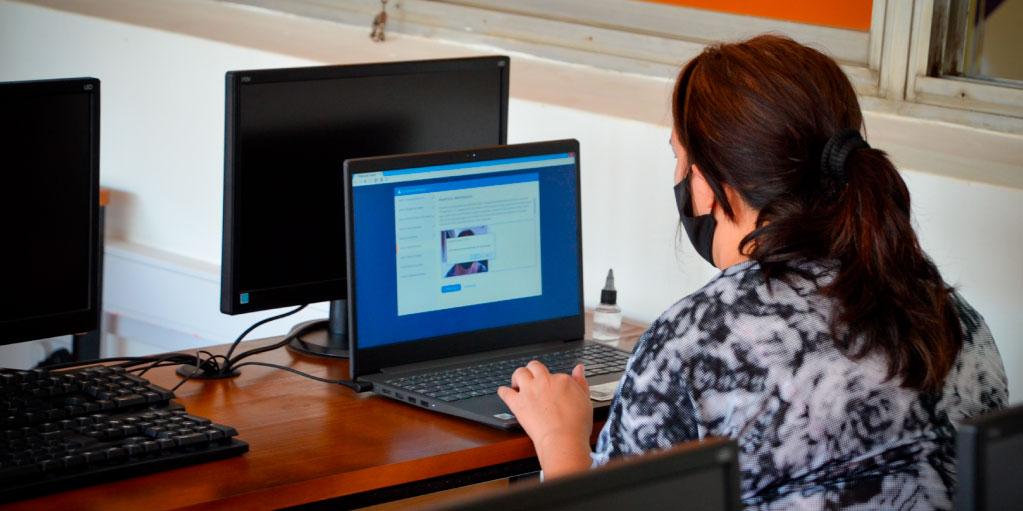 Una estudiante con barbijo frente a una computadora