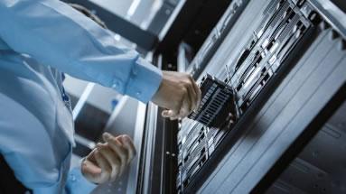 Una persona introduce un dispositivo en una serie de servidores