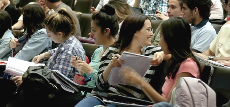 Cinco estudiantes mujeres sentadas con cuadernos en sus manos y una de ellas mira sonriente hacia atrás