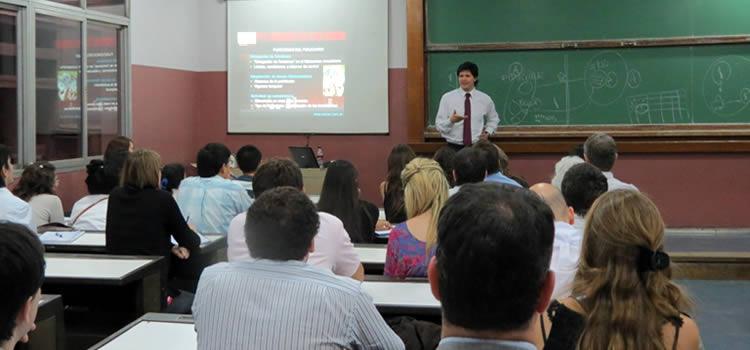 Imagen de un docente con corbata frente a un curso con muchos estudiantes