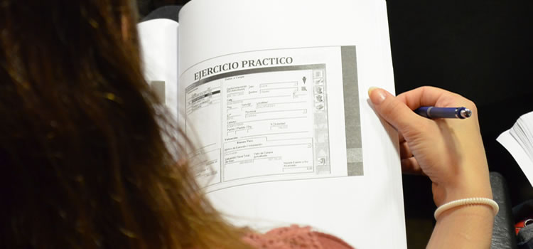 Un cuaderno de apunte sobre las piernas de una mujer quien tiene una lapicera en su mano mientras sostiene el cuaderno