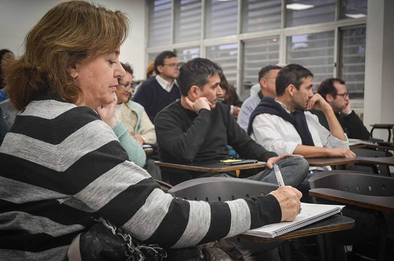 Una profesora escribe en un cuaderno y detrás hay una decena de docentes sentados