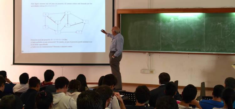 Un docente en una clase frente a una treintena de estudiantes señalando una pantalla con unos gráficos