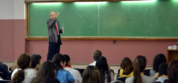 Un docente señala mientras habla a un auditorio con una veintena de alumnos
