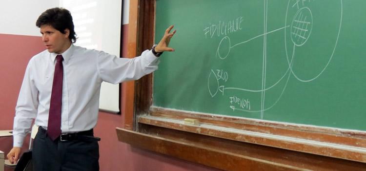 Imagen de un profesor junto a un pizarrón verde escrito con tiza blanca