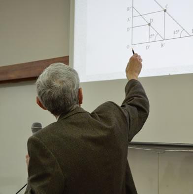 Un docente señala un gráfico de ejes cartesianos en la pizarra