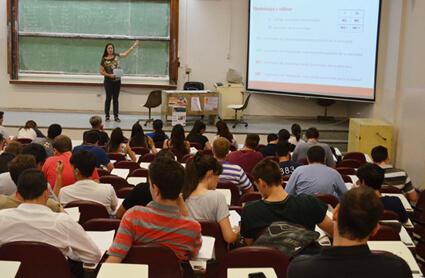 Una docente en un aula explicando una filmina frente a una treintena de estudiantes