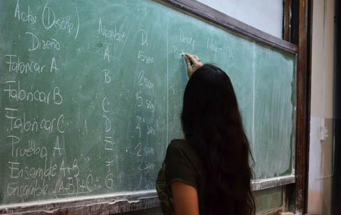 Una docente con cabello largo escribe en un pizarrón con una tiza