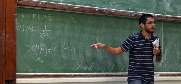 Un docente señalando la pizarra con un cuaderno en la mano