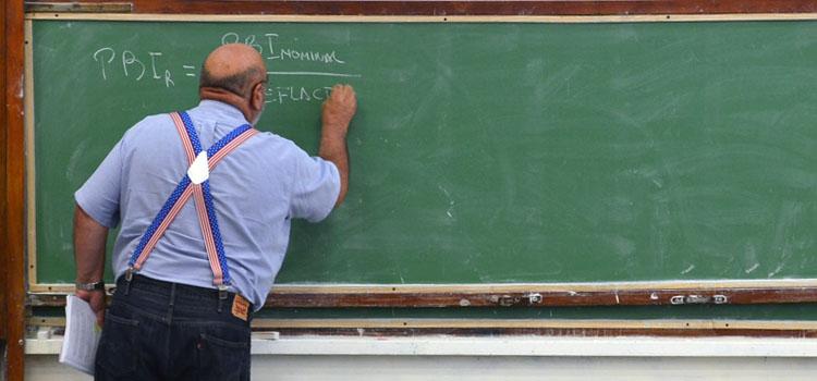 Un docente con tiradores escribe en una pizarra