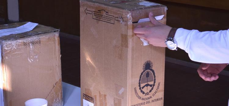 Una urna y una mano de un elector introduciendo un voto