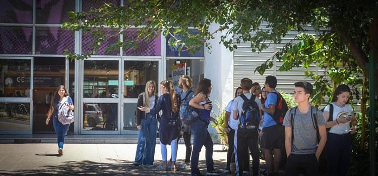 Imagen de estudiantes de la Facultad de Ciencias Económicas en el frente del edificio