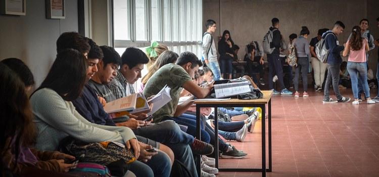 Imagen de estudiantes sentados y de pie en el espacio de acceso al aula O de la planta baja del edificio