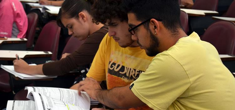 Dos estudiantes leyendo un apunte en un aula de la Facultad mientras detrás una estudiante escribe en un cuaderno