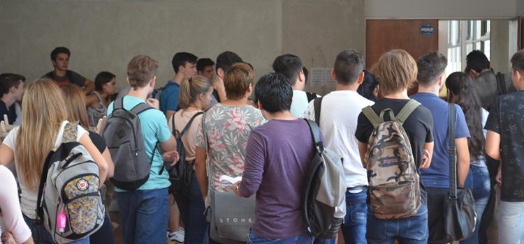 Estudiantes de pie aguardando ingresar a un aula de la Facultad