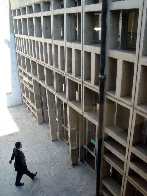 Uno de los costados del edificio de la Facultad donde una mujer está caminando para entrar por la puerta