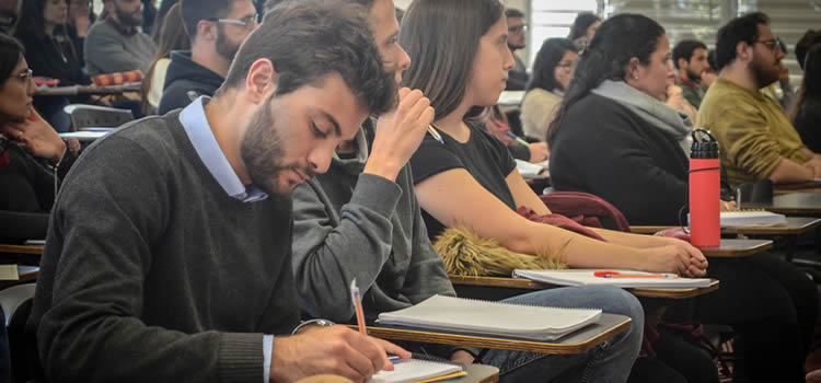 Un profesor joven varón escribiendo sobre una hoja y detrás una veintena de profesores jovenes también sentados