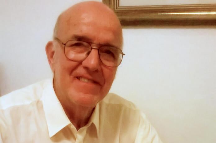 Luis Eugenio Di Marco con anteojos vistiendo una camisa y sonriendo, detrás de una pared que tiene un cuadro