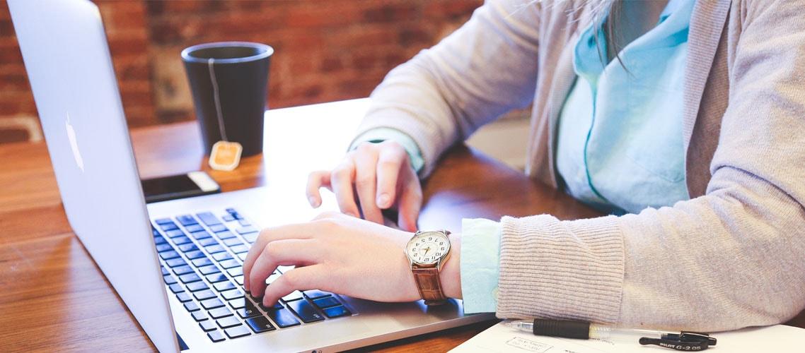 Una mujer tipeando en una computadora portátil con una taza de té sobre el escritorio